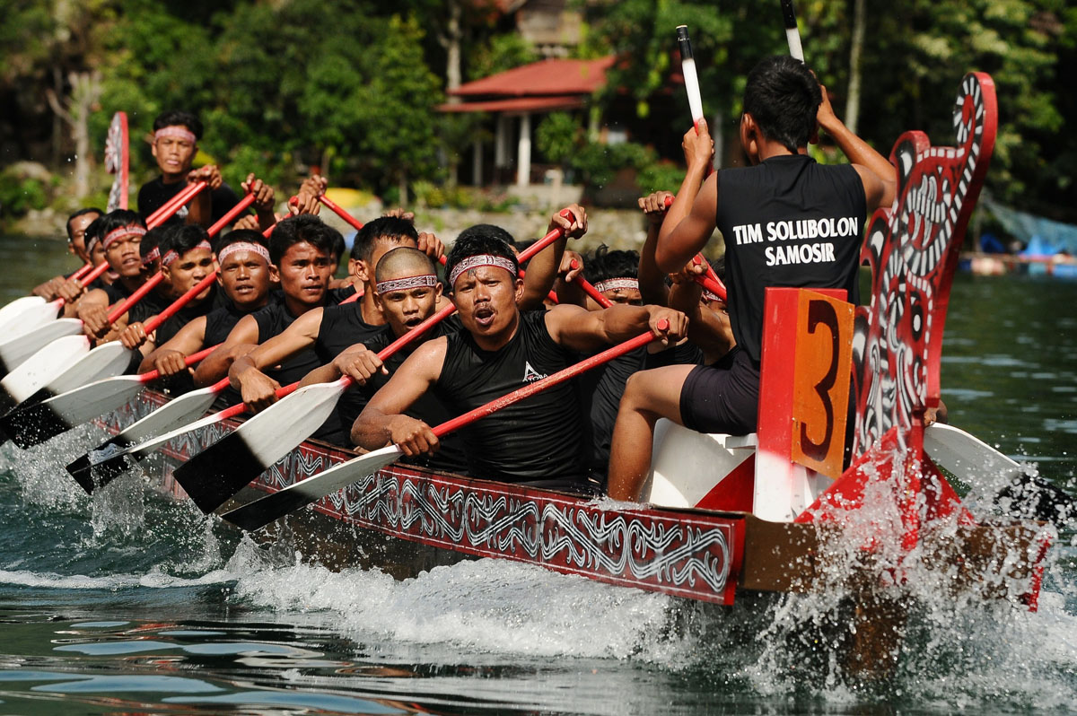 MEDAN, SUMATRA, INDONESIA - SEPTEMBER 13: Solu Bolon Royal boat athletes in action during the competition as part of Lake Toba Festival 2013 on September 13, 2013 in Medan, Sumatra, Indonesia. Lake Toba Festival is a historical tradition to preserve Lake Toba cultural creativity, environment, and communities which are displayed professionally in a festival package. The iconic events are World Drum Festival, World Super Swim around the Samosir, Sigale-gale Carnival, Solu Bolon Royal boat racing, Water and ground paragliding, and Batak Tradition. (Photo by Robertus Pudyanto/Getty Images) ORG XMIT: 180423729